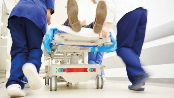 patient-being-pushed-on-hospital-bed-by-two-doctors-wearing-scrubs